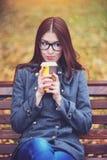 Jovem mulher bonita que senta-se em um café bebendo do banco ou em um revestimento quente do outono do chá na primavera que aprec Imagens de Stock