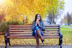 Jovem mulher bonita que senta-se em um café bebendo do banco ou em um revestimento quente do outono do chá na primavera que aprec Imagens de Stock Royalty Free