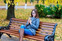 Jovem mulher bonita que senta-se em um café bebendo do banco ou em um revestimento quente do outono do chá na primavera que aprec Imagem de Stock Royalty Free