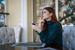 Jovem mulher bonita que senta-se em um café em uma rua na cidade imagens de stock