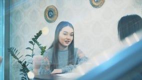 Jovem mulher bonita que senta-se em um caf? Um tiro agradável e morno de uma menina caucasiano na roupa ocasional através de um v vídeos de arquivo