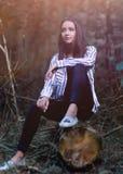 Jovem mulher bonita que senta-se em um log Foto de Stock
