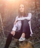 Jovem mulher bonita que senta-se em um log Imagem de Stock