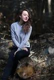 Jovem mulher bonita que senta-se em um log Fotos de Stock Royalty Free