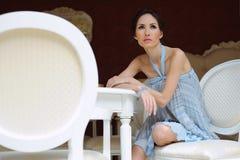 Jovem mulher bonita que senta-se em uma cadeira com um chá do oj do copo no interior refinado fotografia de stock royalty free
