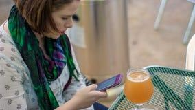 Jovem mulher bonita que senta-se em uma tabela com uma cerveja que datilografa um te imagens de stock royalty free