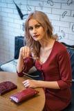 Jovem mulher bonita que senta-se em uma tabela com um caderno e um telefone foto de stock