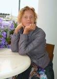 Jovem mulher bonita que senta-se em uma tabela do café do passeio fotografia de stock