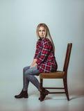 Jovem mulher bonita que senta-se na cadeira Fotos de Stock Royalty Free