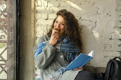 Jovem mulher bonita que senta-se na cafetaria imagens de stock royalty free