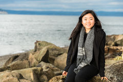 Jovem mulher bonita que senta-se na madeira lançada costa da praia imagem de stock