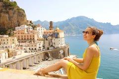 Jovem mulher bonita que senta-se na parede com vista panorâmica do Atr imagem de stock