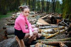 Jovem mulher bonita que senta-se na pilha de troncos de árvore abatidos na floresta foto de stock