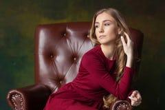Jovem mulher bonita que senta-se na poltrona indoor Vista afastado foto de stock