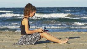 Jovem mulher bonita que senta-se na praia e que derruba em seu PC da tabuleta em um dia de verão video estoque