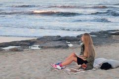 Jovem mulher bonita que senta-se na praia, olhando ondas imagens de stock royalty free