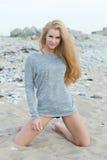 Jovem mulher bonita que senta-se na rocha Fotografia de Stock Royalty Free
