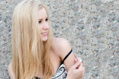 Jovem mulher bonita que senta-se na rocha Fotografia de Stock