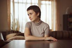 Jovem mulher bonita que senta-se na tabela imagens de stock royalty free
