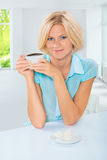 Jovem mulher bonita que senta-se na tabela que guarda a xícara de café e Imagem de Stock