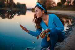 Jovem mulher bonita que senta-se no banco de rio do outono que espirra a água e que guarda ramos fotografia de stock