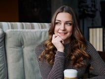 Jovem mulher bonita que senta-se no café italiano do estilo com o copo de Imagem de Stock