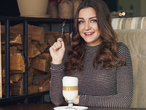 Jovem mulher bonita que senta-se no café italiano do estilo com o copo de imagens de stock royalty free