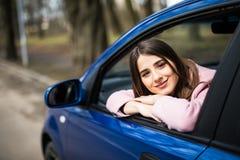 A jovem mulher bonita que senta-se no olhar do carro suporta sobre da janela imagem de stock royalty free