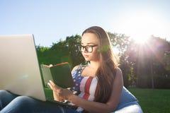 Jovem mulher bonita que senta-se no portátil do uso do saco de feijão ao descansar na grama no parque no sol imagens de stock