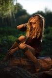 Jovem mulher bonita que senta-se no registro Imagens de Stock