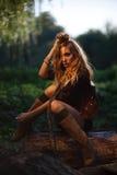 Jovem mulher bonita que senta-se no registro Fotos de Stock Royalty Free