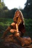 Jovem mulher bonita que senta-se no registro Imagens de Stock Royalty Free