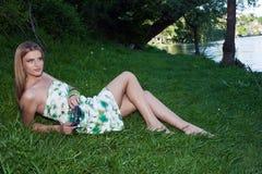 Jovem mulher bonita que senta-se pelo rio imagens de stock