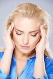 Jovem mulher bonita que sofre de uma dor de cabeça Fotografia de Stock