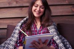 Jovem mulher bonita que sorri ao fazer anotações em um jotter foto de stock royalty free