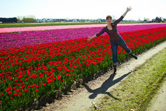 Jovem mulher bonita que tem o divertimento no prado com as tulipas vermelhas e amarelas das flores, fora Fotografia de Stock Royalty Free