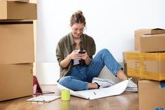 Jovem mulher bonita que texting com seu telefone celular ao sentar-se em sua casa nova foto de stock