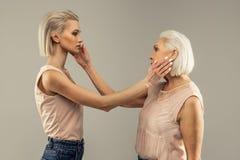 Jovem mulher bonita que toca em sua cara das m?es foto de stock royalty free