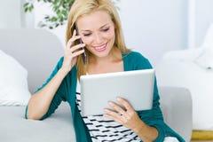 Jovem mulher bonita que trabalha e que usa seu telefone celular Imagem de Stock