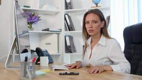 Jovem mulher bonita que trabalha no escritório E não encontra a informação vídeos de arquivo
