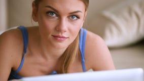 Jovem mulher bonita que trabalha no laptop, sorrindo na câmera video estoque