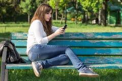 Jovem mulher bonita que usa o smartphone que senta-se no banco Imagens de Stock