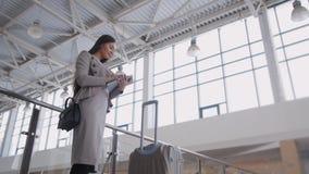 Jovem mulher bonita que usa o tablet pc no aeroporto Mulher de negócios elegante no terminal com plano de espera da mala de viage Imagens de Stock