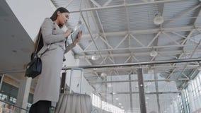 Jovem mulher bonita que usa o tablet pc no aeroporto Mulher de negócios elegante no terminal com plano de espera da mala de viage Foto de Stock