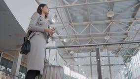 Jovem mulher bonita que usa o tablet pc no aeroporto Mulher de negócios elegante no terminal com plano de espera da mala de viage Imagem de Stock