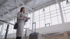 Jovem mulher bonita que usa o tablet pc no aeroporto Mulher de negócios elegante no terminal com plano de espera da mala de viage Fotos de Stock