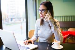 Jovem mulher bonita que usa o telefone celular ao trabalhar com seu portátil na cafetaria Imagens de Stock Royalty Free