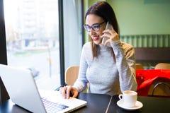 Jovem mulher bonita que usa o telefone celular ao trabalhar com seu portátil na cafetaria Fotografia de Stock