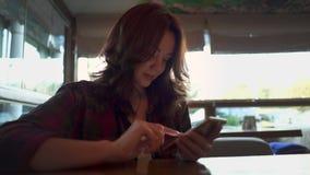 Jovem mulher bonita que usa o telefone celular no café video estoque