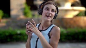 Jovem mulher bonita que usa o telefone esperto, mensagens de datilografia, escutando a música, café bebendo ao andar no urbano video estoque